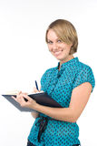 Smiling secretary. The beautiful girl writes in the daily log Royalty Free Stock Photo