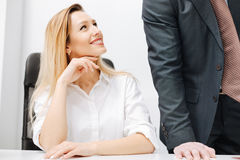 Smiling secretary flirting in the office. Obviously flirting with you. Charming positive smiling secretary sitting in the office while expressing charm and Royalty Free Stock Image