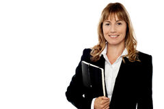 Smiling secretary holding note book. Pretty female executive holding notebook Royalty Free Stock Photo