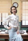 Smiling secretary leaning on desk Royalty Free Stock Photography