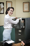 Smiling secretary searching files in the filing cabinet. Smiling vintage secretary searching files in the filing cabinet drawers stock photos