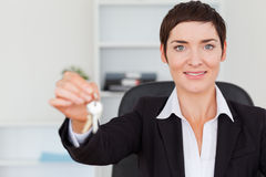 Smiling secretary showing keys Royalty Free Stock Photo