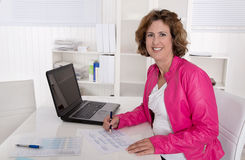 Smiling secretary sitting satisfied at desk at office. Stock Photo