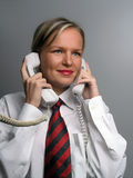 Smiling secretary with two phone Stock Photography
