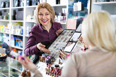 Smiling  seller helps customers choose cosmetics Royalty Free Stock Image
