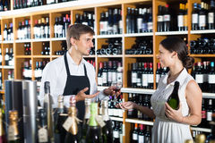 Smiling seller man giving sample taste of wine. Smiling seller men wearing apron giving sample taste of wine in glass to women customer in wine store Stock Photos