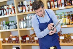 Smiling seller man wearing apron in wine store. Liquor Stock Images
