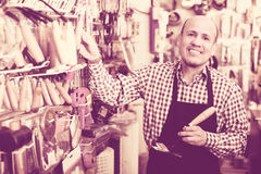 Smiling seller near stand with garden tooling Stock Images