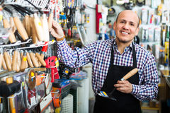 Smiling seller near stand with garden tooling Stock Photo