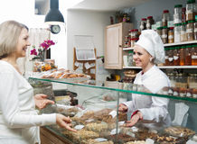 Smiling seller offering sweets. To senior women in local confectionery stock image