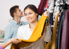 Smiling seller offers dress. Smiling seller offers yellow dress royalty free stock images