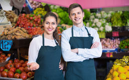 Smiling sellers having vegetables and fruits on displays Royalty Free Stock Image