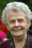 Smiling Senior. Elderly woman smiles while sitting in a garden Stock Images