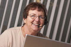 Smiling Senior Adult Woman with Telephone Headset and Monitor Stock Images