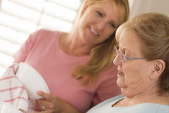 Senior Adult Woman and Young Daughter Talking in Kitchen Stock Photography