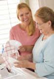 Senior Adult Woman and Young Daughter Talking in Kitchen Stock Image