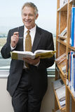 Smiling Senior Business Man In Library Stock Photography