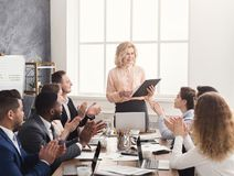 Smiling female boss and team clapping hands at meeting. Smiling senior business women boss and team clapping hands at meeting, celebrating business success or royalty free stock photo