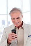 Smiling senior businessman sending a message Royalty Free Stock Photo