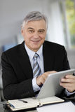 Smiling senior businessman with tablet Stock Image