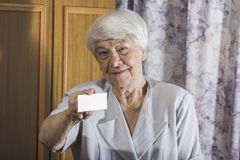 Smiling senior businesswoman holding blank empty business card o Royalty Free Stock Images