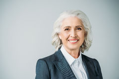 Smiling senior businesswoman in suit on grey royalty free stock images
