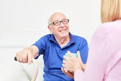 Smiling senior is cared for in home care. Smiling senior with a mug of coffee being cared for in home care Royalty Free Stock Photo