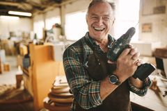 Smiling senior carpenter holding drill machine. Against workshop. Mature male worker smiling confidently to the camera holding drilling machine at his carpentry royalty free stock photos