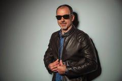 Smiling senior casual man closing his leather jacket Stock Photos