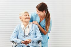 Smiling senior citizen in wheelchair and nurse Royalty Free Stock Photo