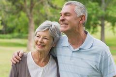 Smiling senior couple with arms around at park Stock Photos