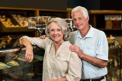 Smiling senior couple at the bakery store Royalty Free Stock Photo