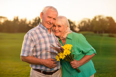 Smiling senior couple with bouquet Stock Image
