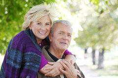 Smiling senior couple. Close-up portrait of smiling eldely women embraching old men while happy senior couple sitting at park Royalty Free Stock Image