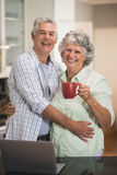 Smiling senior couple with coffee cup standing by laptop at home. Portrait of smiling senior couple with coffee cup standing by laptop at home Stock Image
