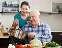 Smiling senior couple cooking food together Royalty Free Stock Images