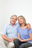 Smiling senior couple on couch. Smiling senior couple sitting together on couch at home Royalty Free Stock Photography
