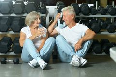 Smiling senior couple. Drinking water after exercising in gym stock image