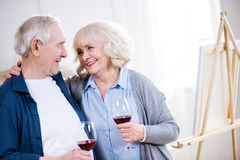 Smiling senior couple drinking wine in art workshop. Portrait of smiling senior couple drinking wine in art workshop Stock Photos