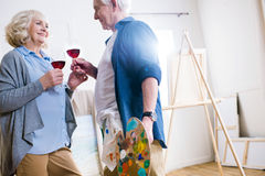 Smiling senior couple drinking wine in art workshop. Side view of smiling senior couple drinking wine in art workshop Royalty Free Stock Image