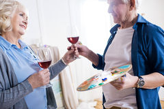 Smiling senior couple drinking wine in art workshop. Side view of smiling senior couple drinking wine in art workshop Royalty Free Stock Photo