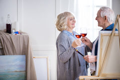 Smiling senior couple drinking wine in art workshop. Side view of smiling senior couple drinking wine in art workshop Royalty Free Stock Photos