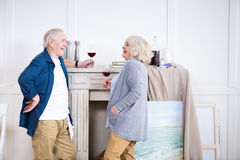 Smiling senior couple drinking wine in art workshop. Side view of smiling senior couple drinking wine in art workshop Stock Images