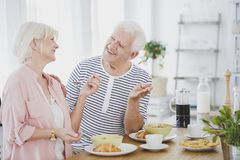 Smiling senior couple eating croissants Royalty Free Stock Photography