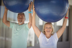 Smiling senior couple exercising with exercise ball. Portrait of smiling senior couple lifting exercise ball while exercising Royalty Free Stock Images