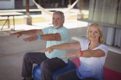 Smiling senior couple exercising on exercise ball. Portrait of smiling senior couple exercising on exercise ball at veranda Royalty Free Stock Photography