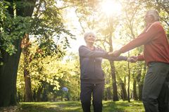 Senior couple in forest holding hands and rotate in circ royalty free stock image