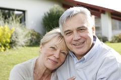 Smiling senior couple in front of their new house. Smiling senior couple sitting in garden Stock Photos