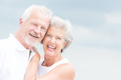 Smiling senior couple. Happy and smiling couple in front of cloudy sky Royalty Free Stock Images