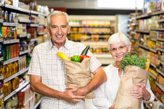 Smiling senior couple holding grocery bags Royalty Free Stock Image